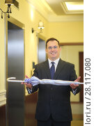 Handsome man in a business suit and tie holds a silver umbrella in the hallway near the elevator. Стоковое фото, фотограф Losevsky Pavel / Фотобанк Лори