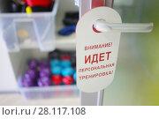 Купить «Door handle and text - Attention! Personal training! in fitness center», фото № 28117108, снято 22 октября 2016 г. (c) Losevsky Pavel / Фотобанк Лори