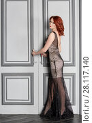 Купить «Red-haired young woman in white and black suit stands in room, holding door handles», фото № 28117140, снято 14 ноября 2015 г. (c) Losevsky Pavel / Фотобанк Лори