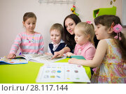 Купить «Four children are reading books with a young woman, focus on younger girl», фото № 28117144, снято 28 апреля 2015 г. (c) Losevsky Pavel / Фотобанк Лори