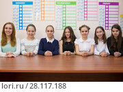 Купить «Seven young girls are sitting at the table next to schedule», фото № 28117188, снято 28 апреля 2015 г. (c) Losevsky Pavel / Фотобанк Лори
