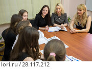 Купить «Young three teachers (focus on woman in gray dress) are sitting at table with books and talking to five students in classroom», фото № 28117212, снято 28 апреля 2015 г. (c) Losevsky Pavel / Фотобанк Лори
