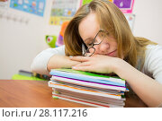 Купить «Tired young girl is sleeping with glasses on the textbooks», фото № 28117216, снято 28 апреля 2015 г. (c) Losevsky Pavel / Фотобанк Лори