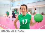 Smiling woman in green holds ball in gym during volleyball game, playing people out of focus. Стоковое фото, фотограф Losevsky Pavel / Фотобанк Лори