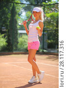 Купить «Happy girl in shorts stands with racket on court at sunny summer day», фото № 28117316, снято 24 июня 2016 г. (c) Losevsky Pavel / Фотобанк Лори