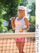 Купить «Girl in cap stands with tennis racket and ball on sport playground outdoor», фото № 28117340, снято 24 июня 2016 г. (c) Losevsky Pavel / Фотобанк Лори