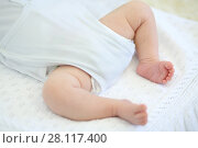 Купить «Barefoot legs of cute sleeping baby on white plaid in studio», фото № 28117400, снято 27 августа 2016 г. (c) Losevsky Pavel / Фотобанк Лори