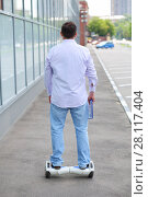 Купить «Man in jeans rides GyroScooter on street at sunny summer day, back view», фото № 28117404, снято 25 июня 2016 г. (c) Losevsky Pavel / Фотобанк Лори