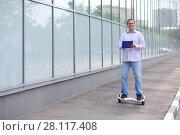 Купить «Man with folder rides gyroscooter on street at sunny summer day», фото № 28117408, снято 25 июня 2016 г. (c) Losevsky Pavel / Фотобанк Лори