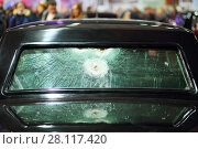 Купить «Rear black car window with traces of shots at exhibition, shallow dof, crowd out of focus», фото № 28117420, снято 7 марта 2016 г. (c) Losevsky Pavel / Фотобанк Лори