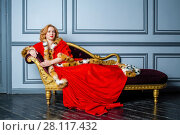 Купить «Blonde woman in red dress and cloak lies on couch in room», фото № 28117432, снято 14 ноября 2015 г. (c) Losevsky Pavel / Фотобанк Лори