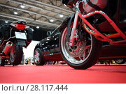 Купить «Black bikes for cortege, car are on red carpet in exhibition, close up», фото № 28117444, снято 7 марта 2016 г. (c) Losevsky Pavel / Фотобанк Лори