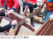 Купить «Hands of two men sawn timber at national fair outdoor, noface», фото № 28117464, снято 12 марта 2016 г. (c) Losevsky Pavel / Фотобанк Лори
