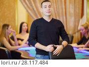 Купить «Young man in black poses in casino, four women play poker out of focus», фото № 28117484, снято 24 октября 2016 г. (c) Losevsky Pavel / Фотобанк Лори
