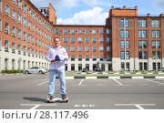 Купить «Happy man with documents rides gyroscooter near building at sunny summer day», фото № 28117496, снято 25 июня 2016 г. (c) Losevsky Pavel / Фотобанк Лори