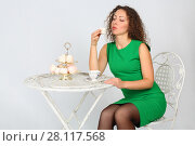 Купить «Pretty woman in green holds marshmallow souffle at table in white studio», фото № 28117568, снято 20 ноября 2015 г. (c) Losevsky Pavel / Фотобанк Лори