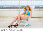 Купить «Portrait of a girl in a blue swimsuit on a lounger on the roof of a multistory building», фото № 28117588, снято 30 июля 2015 г. (c) Losevsky Pavel / Фотобанк Лори