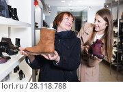 Купить «Smiling girl and adult woman are choosing autumn shoes», фото № 28118788, снято 13 декабря 2017 г. (c) Яков Филимонов / Фотобанк Лори