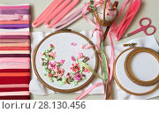 Купить «Top view on the embroidery process with satin ribbons of spring flowers in a pink gamma and an accessories for needlework», фото № 28130456, снято 27 февраля 2018 г. (c) Виктория Катьянова / Фотобанк Лори