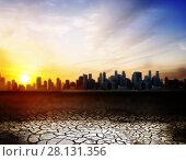 Купить «cracked desert surface over sunset in city», фото № 28131356, снято 18 февраля 2015 г. (c) Syda Productions / Фотобанк Лори