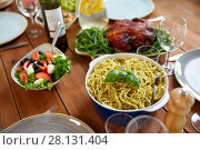 Купить «pasta with basil in bowl and other food on table», фото № 28131404, снято 5 октября 2017 г. (c) Syda Productions / Фотобанк Лори