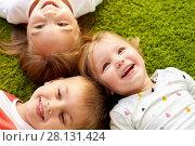 Купить «happy little kids lying on floor or carpet», фото № 28131424, снято 15 октября 2017 г. (c) Syda Productions / Фотобанк Лори