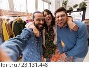 Купить «friends taking selfie at vintage clothing store», фото № 28131448, снято 30 ноября 2017 г. (c) Syda Productions / Фотобанк Лори