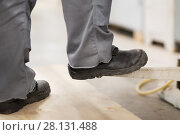 Купить «close up of male worker feet in working shoes», фото № 28131488, снято 10 ноября 2017 г. (c) Syda Productions / Фотобанк Лори