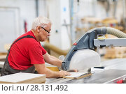 Купить «carpenter with panel saw and fibreboard at factory», фото № 28131492, снято 10 ноября 2017 г. (c) Syda Productions / Фотобанк Лори