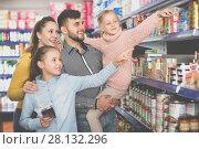 Купить «Happy family with two little girls buying food products in super», фото № 28132296, снято 20 января 2018 г. (c) Яков Филимонов / Фотобанк Лори