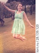 Купить «positive young brunette girl in dress jumping at the garden», фото № 28139120, снято 18 апреля 2017 г. (c) Яков Филимонов / Фотобанк Лори