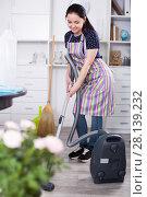 Купить «Young woman with vacuum cleaner», фото № 28139232, снято 9 апреля 2017 г. (c) Яков Филимонов / Фотобанк Лори
