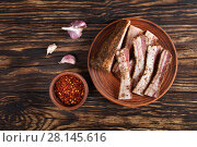 sliced spicy air dried speck on clay plate. Стоковое фото, фотограф Oksana Zh / Фотобанк Лори