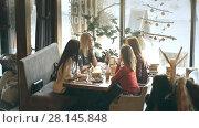 Купить «Group of four young people sitting at table in restaurant and having fun while dining», видеоролик № 28145848, снято 30 января 2018 г. (c) Виктор Аллин / Фотобанк Лори
