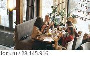 Купить «Four beautiful women sit in cafe with phones», видеоролик № 28145916, снято 30 января 2018 г. (c) Виктор Аллин / Фотобанк Лори