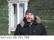 Купить «Мужчина с бородой в зимней одежде на фоне дачного дома», эксклюзивное фото № 28151744, снято 9 марта 2018 г. (c) Елена Коромыслова / Фотобанк Лори