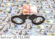 Купить «Steel police handcuffs lying on the background of american dollars with folded stack of banknotes of russian roubles», фото № 28152680, снято 4 января 2017 г. (c) FotograFF / Фотобанк Лори