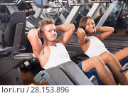 Купить «Well trained happy young man and woman training abdominal muscles in gym», фото № 28153896, снято 4 октября 2016 г. (c) Яков Филимонов / Фотобанк Лори