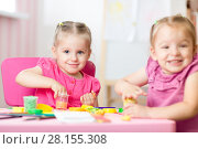 Купить «Two cute preschooler sisters having fun together with colorful modeling clay at a daycare. Creative kids molding in nursery at home. Children playing with plasticine or dough.», фото № 28155308, снято 20 марта 2018 г. (c) Оксана Кузьмина / Фотобанк Лори