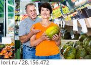Купить «Adult male and female are choosing green melons in the store.», фото № 28156472, снято 22 октября 2017 г. (c) Яков Филимонов / Фотобанк Лори