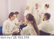 Купить «Group of smiling students medical faculty talking», фото № 28163316, снято 5 октября 2017 г. (c) Яков Филимонов / Фотобанк Лори