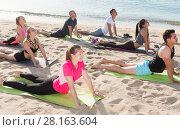 Купить «Sporty people practicing yoga on beach», фото № 28163604, снято 14 июня 2017 г. (c) Яков Филимонов / Фотобанк Лори
