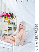 Купить «Attractive blonde sits on white bed with pillows in cozy bedroom», фото № 28170680, снято 20 ноября 2015 г. (c) Losevsky Pavel / Фотобанк Лори