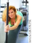 Купить «Happy beautiful woman does exercises on simulator in modern gym, shallow dof», фото № 28170716, снято 29 июня 2016 г. (c) Losevsky Pavel / Фотобанк Лори