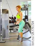 Купить «Beautiful woman does exercises on simulator in gym, shallow dof», фото № 28170724, снято 29 июня 2016 г. (c) Losevsky Pavel / Фотобанк Лори