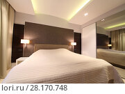 Large bed and wardrobe with mirror in bedroom interior of modern flat. Стоковое фото, фотограф Losevsky Pavel / Фотобанк Лори