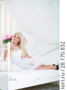 Купить «Happy blonde looks away on white bed with pillows in cozy bedroom», фото № 28170832, снято 20 ноября 2015 г. (c) Losevsky Pavel / Фотобанк Лори