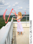 Купить «Beautiful woman in white with red curly ribbon on the roof of a multistory building», фото № 28170840, снято 30 июля 2015 г. (c) Losevsky Pavel / Фотобанк Лори