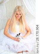 Купить «Blonde in bride white dress holds funny fluffy cub of rabbit on bed», фото № 28170904, снято 20 ноября 2015 г. (c) Losevsky Pavel / Фотобанк Лори