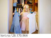 Купить «Little blonde pretty girl in wreath chooses dress in wardrobe at home», фото № 28170964, снято 25 октября 2016 г. (c) Losevsky Pavel / Фотобанк Лори
